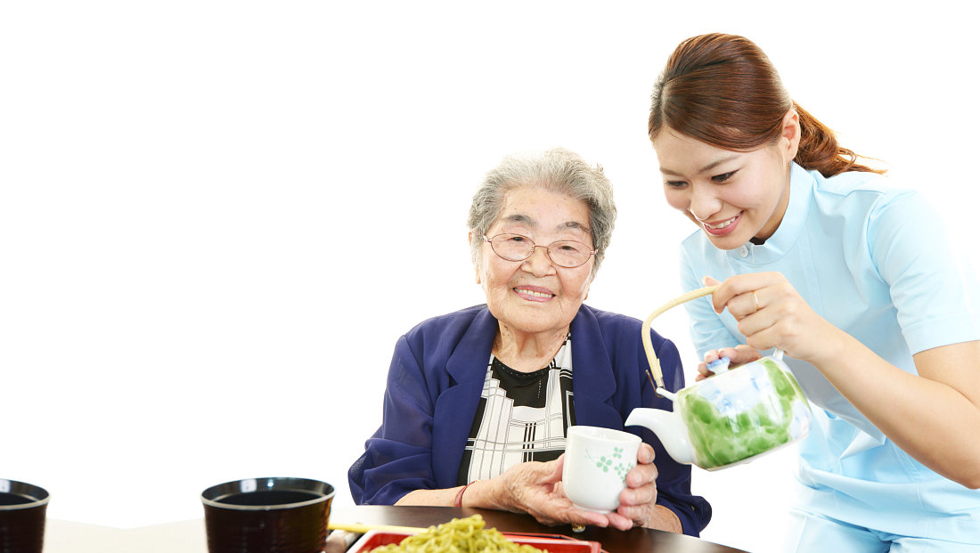 caregiver giving cup of tea to the old woman
